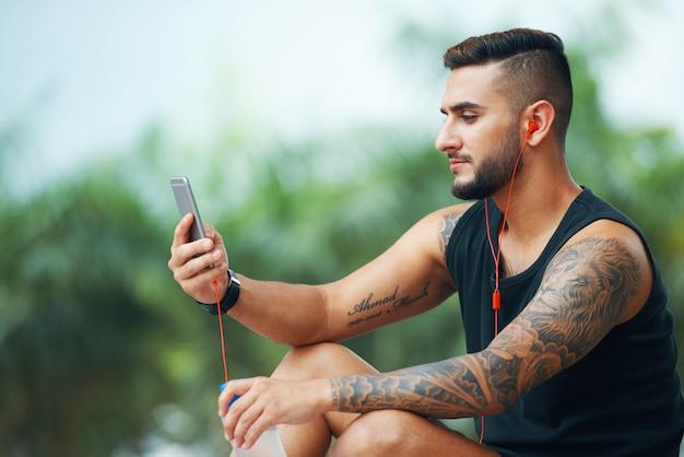 Wytatuowany sportowiec z telefonem na zewnątrz