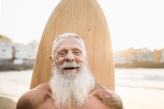 Wytatuowany starszy surfer trzymając rocznika deskę surfingową na plaży o zachodzie słońca - skupić się na twarzy