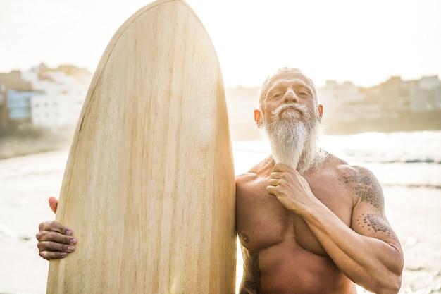 Wytatuowany starszy surfer trzymający starą deskę surfingową na plaży o zachodzie słońca - skup się na twarzy