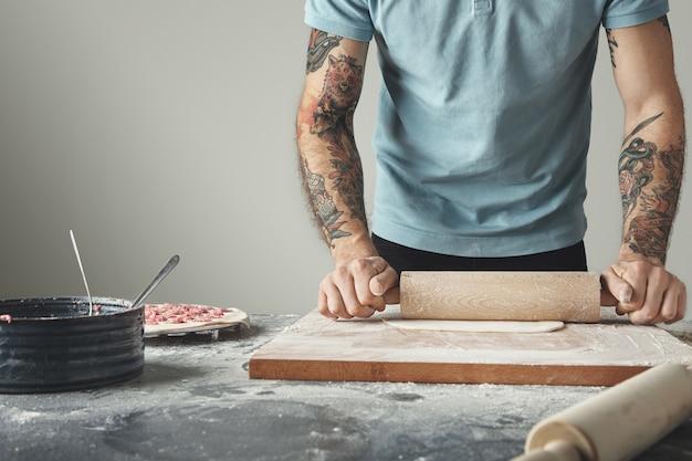 Wytatuowany szef kuchni gotuje pelmeni, pierogi lub ravioli w specjalnej formie.