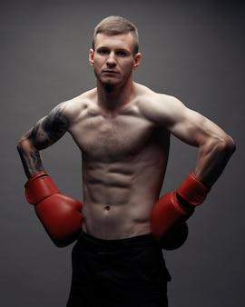 Wytatuuj silny bokser przed ciemnym tłem