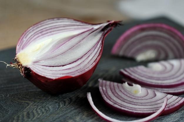 Wytnij czerwoną cebulę na drewnianej desce na drewnianym rustykalnym