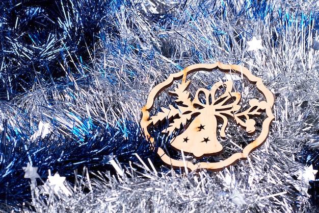 Wytnij drewnianą figurkę dzwonka na świątecznych blichtrach.