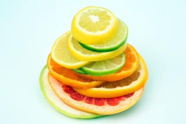 Wytnij kawałki różnych owoców cytrusowych na białym stole
