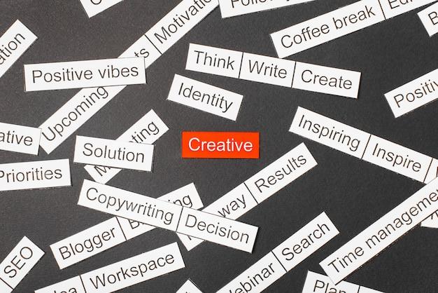 Wytnij papierowy napis kreatywny na czerwonym tle, otoczony innymi napisami na ciemnym tle. koncepcja chmura słowa.