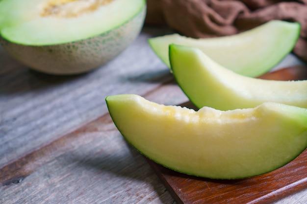 Wytnij świeży słodki zielony melon na drewnianym stole. owoce lub koncepcja opieki zdrowotnej.