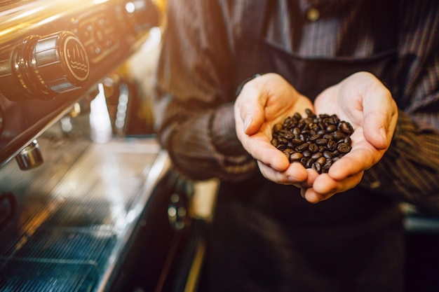 Wytnij widok i zamknij filiżankę mężczyzny trzymającego w rękach ziarna kawy. stoi przy ekspresie do kawy