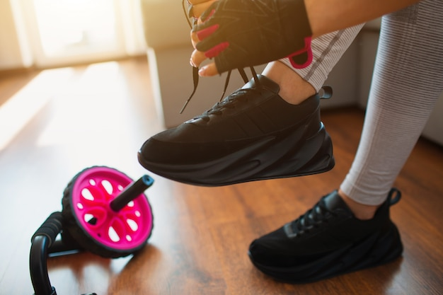 Wytnij widok kobiecych czarnych tenisówek z wiązaniem sznurówek. przygotowanie do treningu w domu. sportowy sprzęt po lewej stronie.