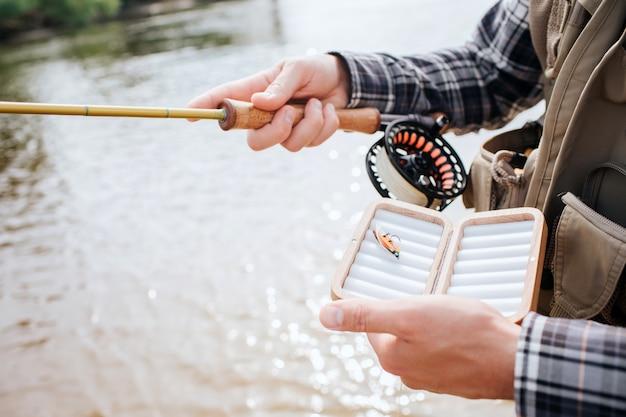 Wytnij widok mężczyzny stojącego w wodzie i trzymającego spinning z kołowrotkiem w jednej ręce i pudełkiem z jedną sztuczną silikonową przynętą wędkarską z drugiej. facet nosi kamizelkę.