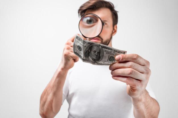 Wytnij widok młodego mężczyzny, który trzyma sto dolarów i patrzy na niego przez lupę. chce mieć pewność, że ten rachunek nie jest fałszywy. pojedynczo na białej ścianie