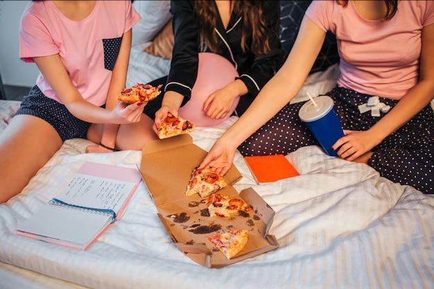Wytnij widok nastolatków siedzących na łóżku i biorących kawałki pizzy. kobiety po prawej trzymają plastikowy kubek z colą. planiści i notebboks są na łóżku. dziewczyny noszą piżamę.