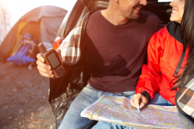 Wytnij widok pięknej pary siedzącej razem w bagażniku i uśmiech. on trzyma telefon satelitarny. ona ma mapę. ludzie są blisko namiotu.