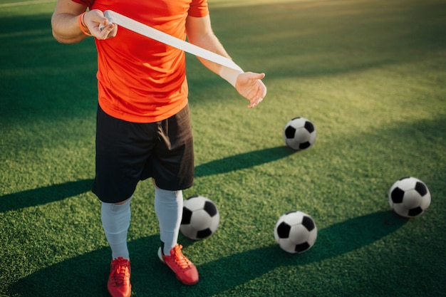 Wytnij widok piłkarza trzymającego bandaż w rękach
