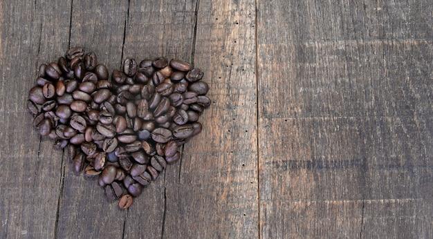 Wytwarzanie w kształcie serca z ziaren kawy ułożonych na rustykalnej desce z miejscem na kopię po prawej stronie