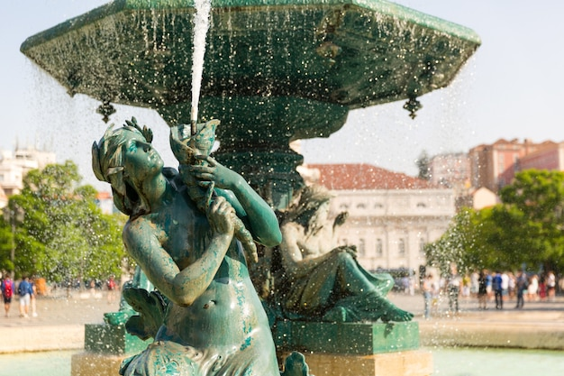 Wytworna fontanna na placu z rzeźbą kobiety, portugalia