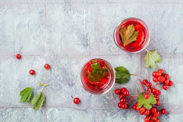 Wywar z dojrzałych jagód kaliny w przezroczystych szklankach i jagód obok niego na stole. medycyna alternatywna, odżywianie witaminowe i wellness. widok z góry