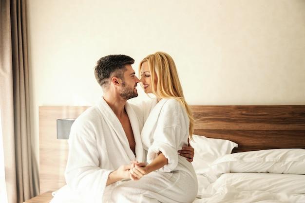 Wywoływanie wspomnień w pokoju hotelowym delikatnym uściskiem i pocałunkiem. piękna uśmiechnięta para, śliczna blondynka i przystojny mężczyzna, w białych szlafrokach, cieszą się łóżkiem z czystym łóżkiem zakochana para urocze ptaki