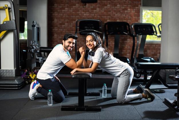 Wyzwanie siłowania się na rękę między młodą indyjską parą azjatów - zabawa na siłowni