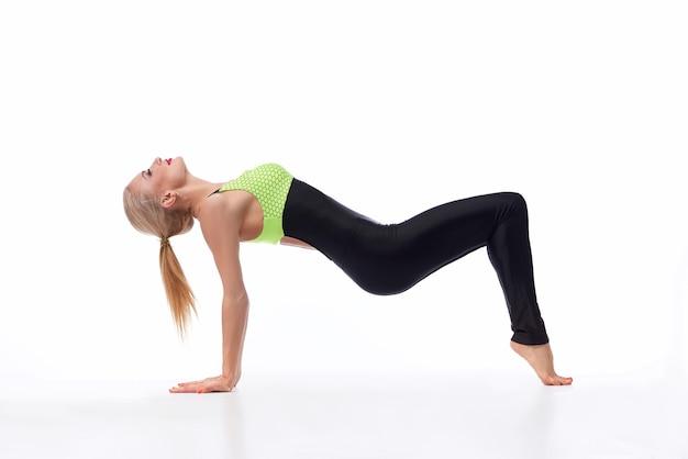 Wyzywanie się w sporcie. portret wysportowanej i stonowanej sportsmenki wykonującej jogę w studio na białym tle copyspace