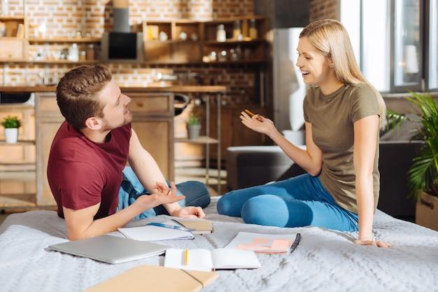 Wzajemne zrozumienie. dobrze wyglądająca, miła, zadowolona para prowadząca badania podczas flirtowania i patrzenia na siebie