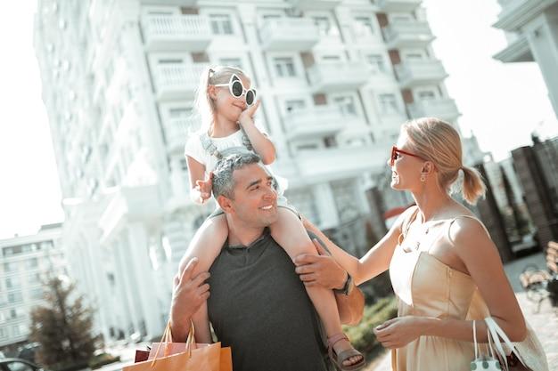 Wzajemne zrozumienie. mała uśmiechnięta dziewczynka rozmawiająca z obojgiem rodziców siedzących na ramionach ojca na spacerze.