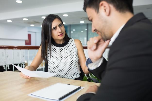 Wzburzona biznesowa dama ubiera pracownika dla błędów