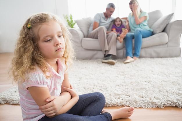 Wzburzona dziewczyny obsiadanie na podłoga podczas gdy rodzice cieszy się z bratem