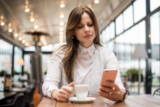 Wzburzona kobieta czyta wiadomość na telefonie w kawiarni.