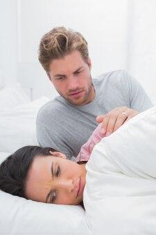 Wzburzona kobieta ignoruje jej partnera w jej łóżku