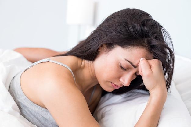 Wzburzona kobieta, leżąc na łóżku