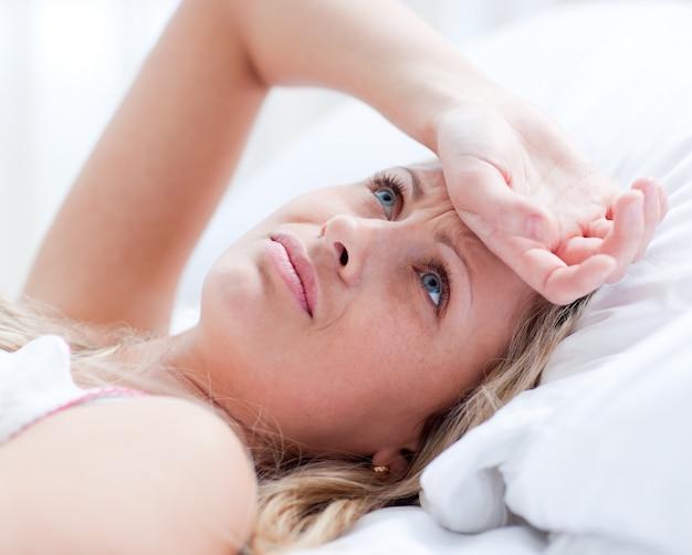 Wzburzona kobieta ma migreny lying on the beach na łóżku