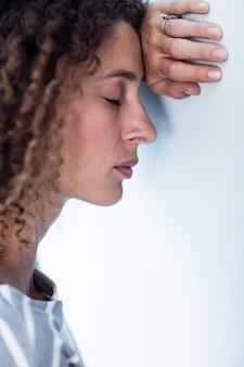 Wzburzona kobieta opiera na ścianie