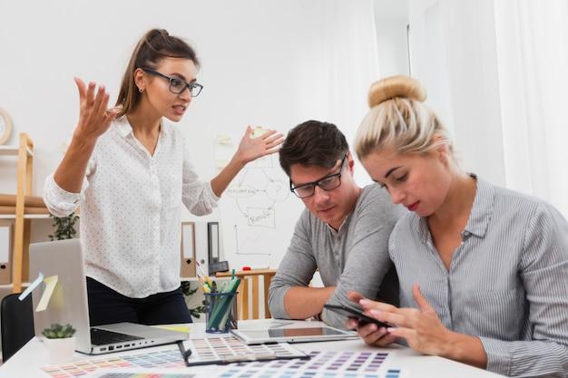 Wzburzona kobieta patrzeje jej partnerów biznesowych