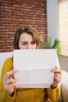 Wzburzona kobieta patrzeje rachunek na leżance w żywym pokoju