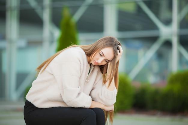 Wzburzona kobieta siedzi na ławce z problemami