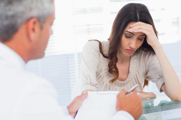 Wzburzona kobieta słucha jej docter opowiada o chorobie