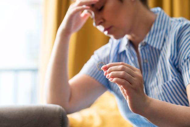 Wzburzona kobieta trzyma obrączkę ślubną