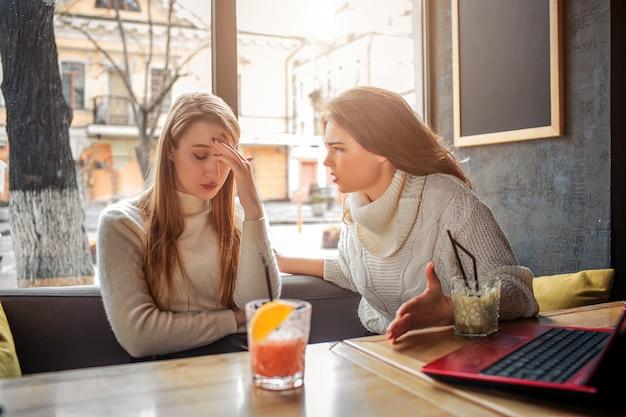 Wzburzona młoda kobieta siedzi przy stołem. zakrywa dłonią twarz i spogląda w dół. jej przyjaciółka patrzy na nią i mówi.