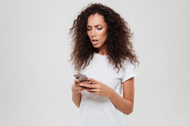 Wzburzona poważna kędzierzawa kobiety writing wiadomość na smartphone