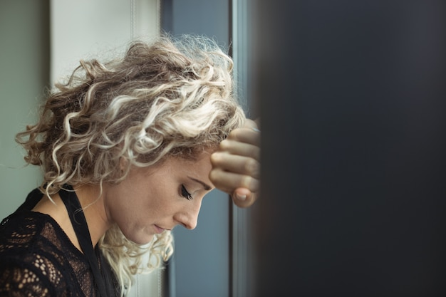 Wzburzony bizneswoman opiera na okno