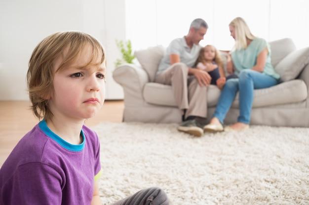 Wzburzony chłopiec obsiadanie na podłoga podczas gdy rodzice cieszy się z siostrą
