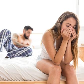 Wzburzony kobiety obsiadanie na łóżku przed jej mężem