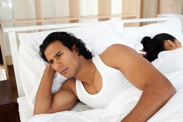 Wzburzony mężczyzna w łóżkowym dosypianiu oddzielny kobieta
