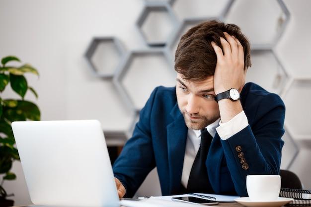 Wzburzony młody biznesmena obsiadanie przy laptopem, biurowy tło.
