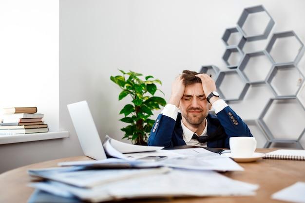 Wzburzony młody biznesmena obsiadanie przy miejscem pracy, biurowy tło.