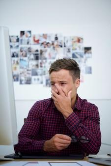 Wzburzony młody człowiek patrzeje ekran komputerowego, zakrywa twarz ręką i płacze