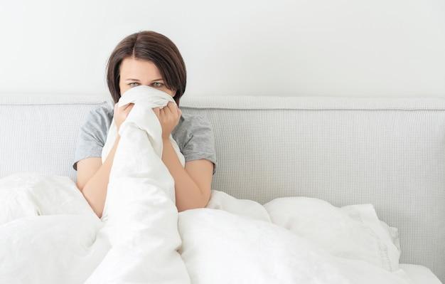 Wzburzony smutny młody brunetki kobiety obsiadanie w łóżku w domu z kopii przestrzenią