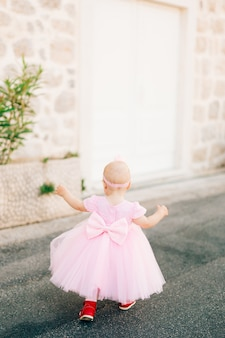 Wzdłuż drogi biegnie urocza dziewczynka w różowej sukience z kokardką i opaską