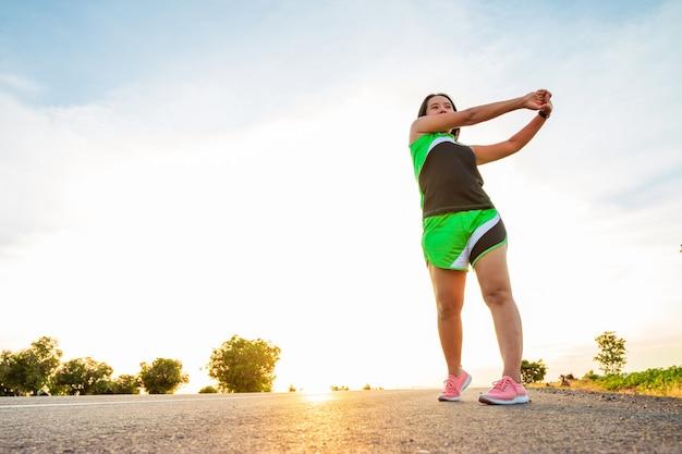Wzdłuż drogi na zboczu wzgórza o zachodzie słońca kobieta ćwiczy, biegając.