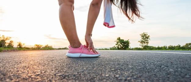 Wzdłuż drogi na zboczu wzgórza w czasie zachodu słońca kobieta ćwiczy biegając.